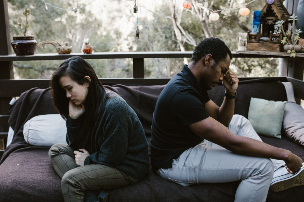 a man and a woman sit on their bed facing away from each other looking upset representing the toll infidelity can take on a relationship. Learn about affair recovery counseling in Cincinnati, OH