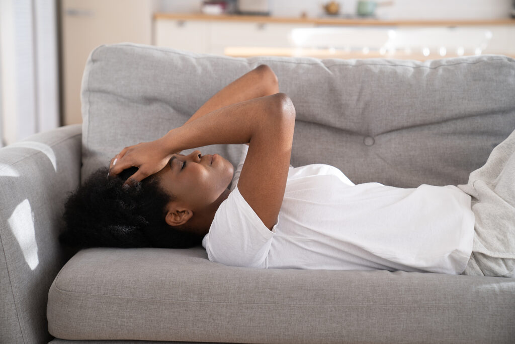 sad woman lays on the couch with her head in her hands before getting dialectical behavior therapy, DBT in Cincinnati, oh